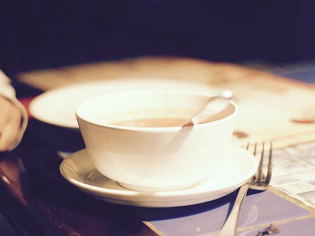 テーブルの上のスープカップとお皿の画像